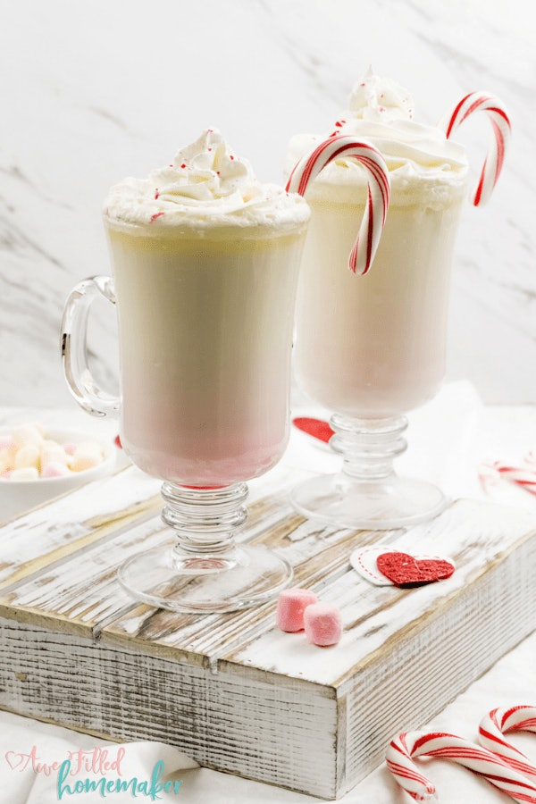 two clear mugs of white hot chocolate with whipped cream and candy canes in the glass