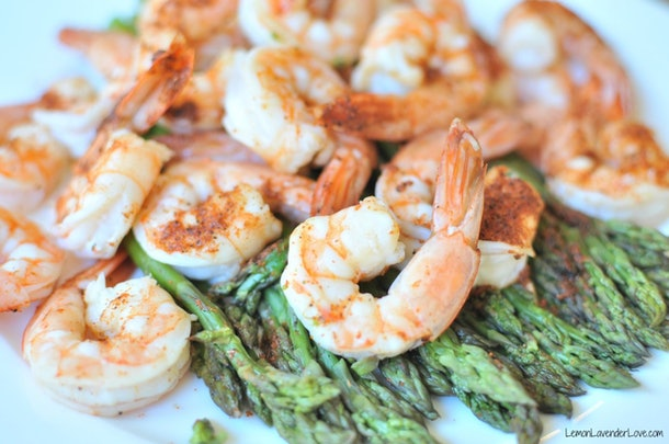 cooked shrimp on a bed of asparagus