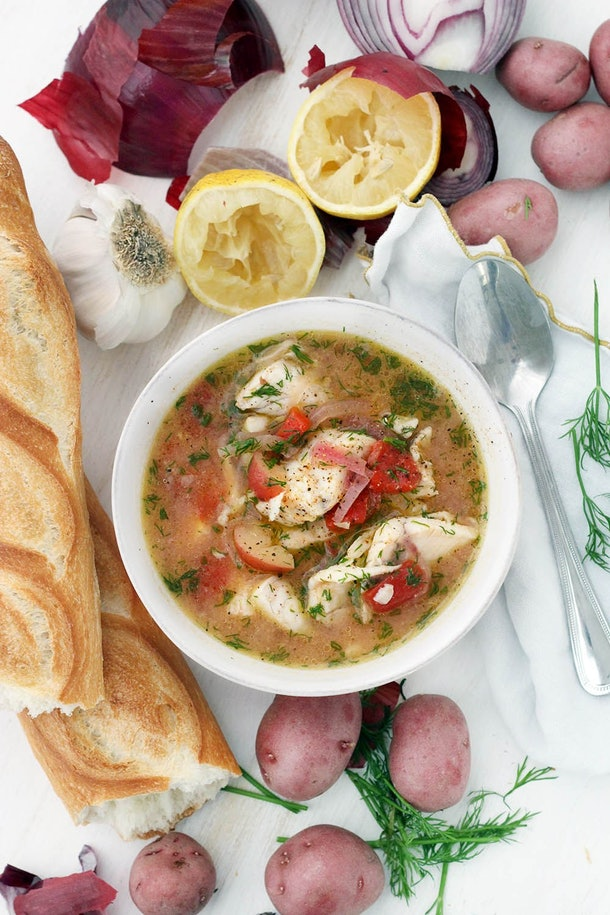 white fish soup in a yellow broth with an assortment of seasoning with fish, potatoes, tomatoes and onions combined in bowl next to loaf of bread and vegetables scattered on table.