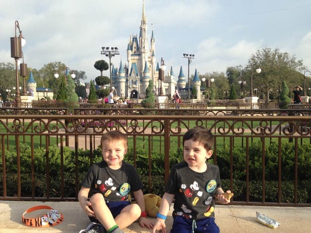 Two boys in front of Cindarella's castle at the Magic Kingdom