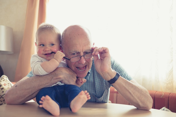 blue-eyed, blonde baby playing with grandfather's glasses