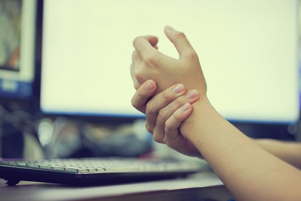 close up of hands massaging themselves at a computer desk