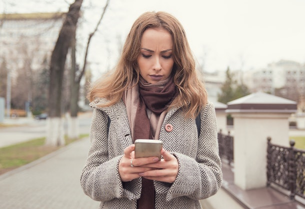A woman looking at her iphone, looking upset.