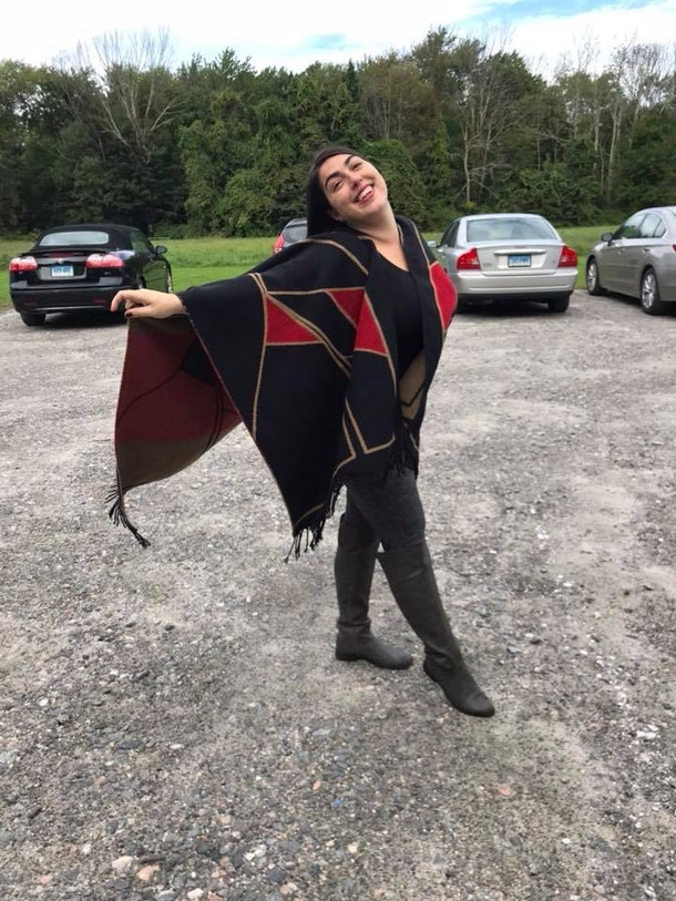 A picture of the writer, a woman in her 30s, posing for the camera with her arms out wearing a black and red shawl, black pants, black boots.