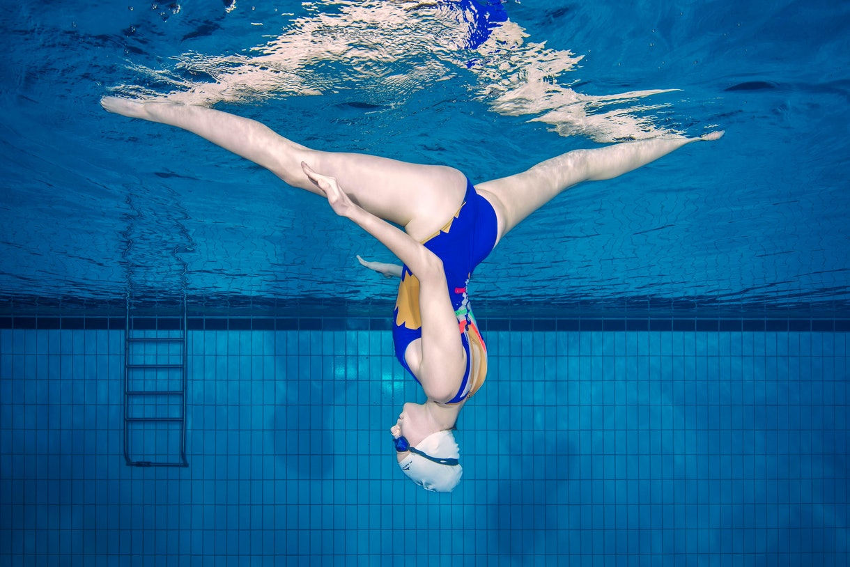 A girl in swimming cap swims upside down with legs in the splits.