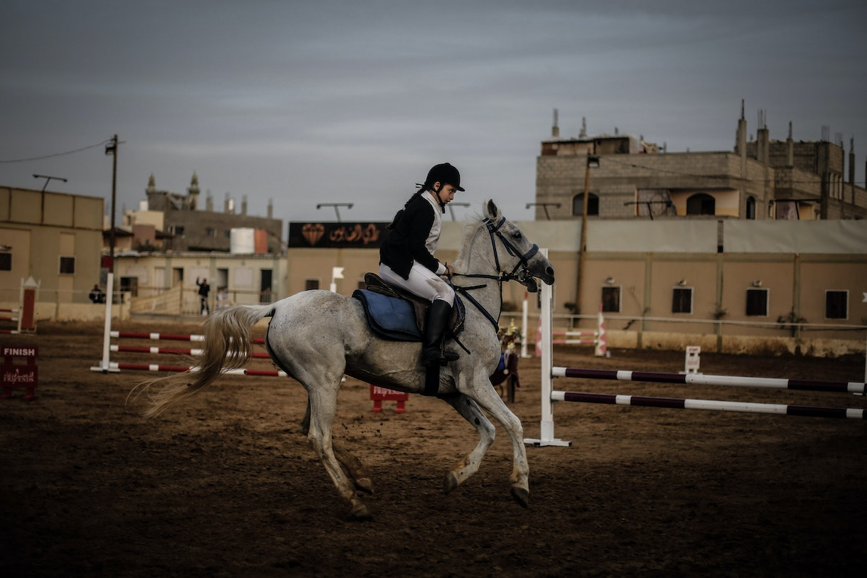 Young Palestinian girl trots around a corral in Gaza on her white horse.