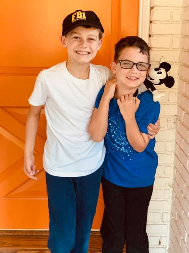 Two brothers standing in front of a front door, arms around one another, smiling.