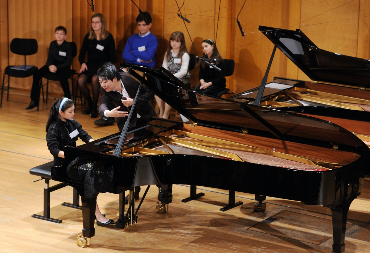Young girl sits at grand piano with teacher hovering over the keys.