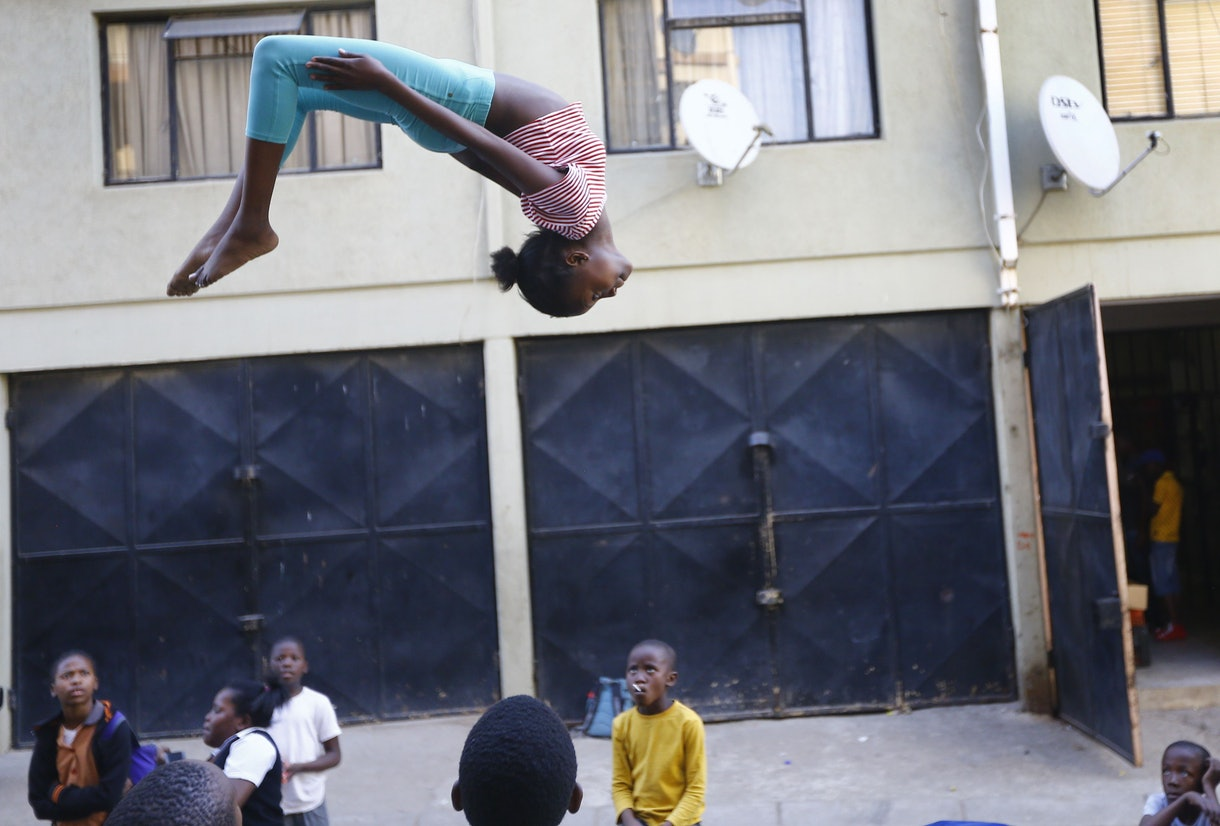 A girl hangs upside down in air with back arched, as she jumps on a trampoline in South Africa.