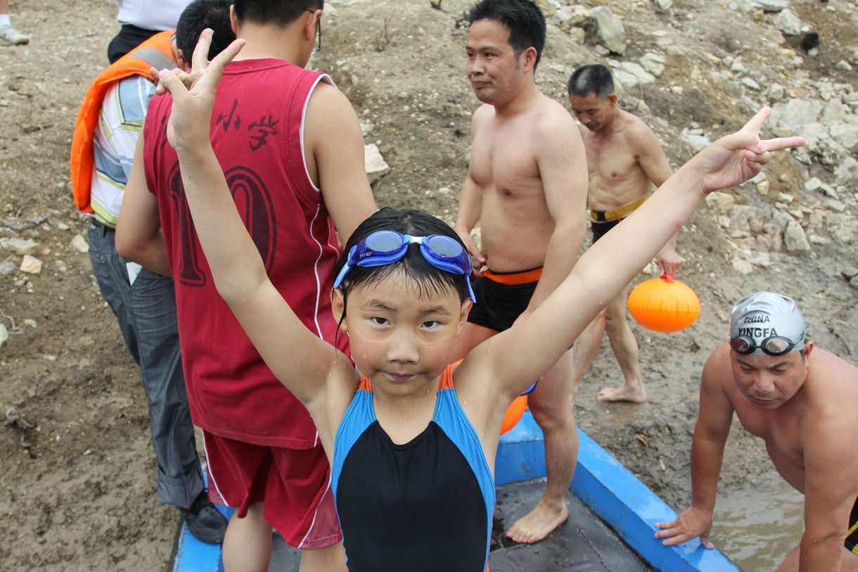 girl in swimmers raises her hands in triumph after crossing river.