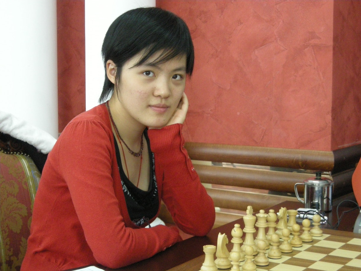 Girl in red sweater sits with arms crossed at chess table.