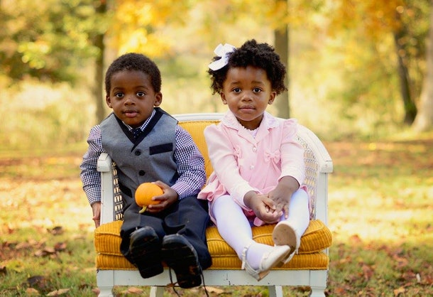 Little girl and little boy sit on tiny sofa on grass.