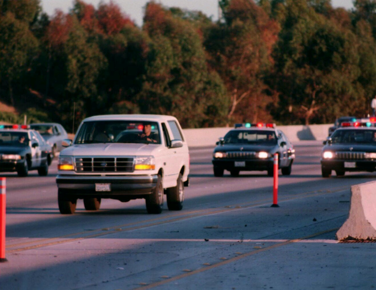O. J. Simpson's Ford Bronco is followed by police in a two hour chase after the murder of his wife Nicole Simpson and her friend Ronald Goldman.