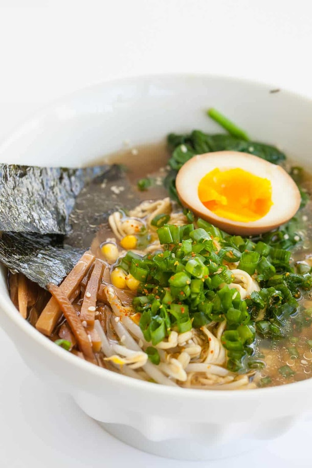 Instant pot ramen noodle soup with chopped green onions, dried seaweed, and a half-boiled egg.