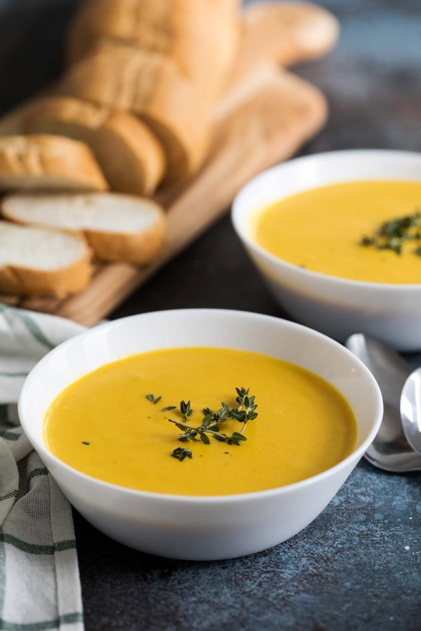 Yellow slow cooker butternut squash soup in white bowl