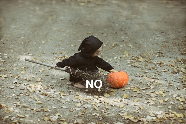 Small child in witch costume plays with broom and pumpkin.