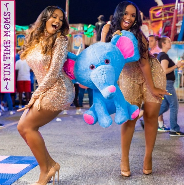 Two Black women pose at a carnival holding a blue stuffed elephant.