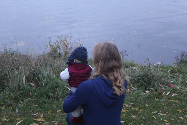 A picture of the author holding her young son, sitting by the side of a lagoon.