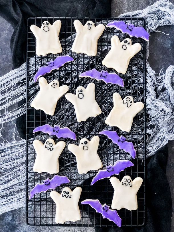 Decorated sugar cookies in the shape of ghosts and bats are perfectly imperfect Halloween snacks for the classroom.
