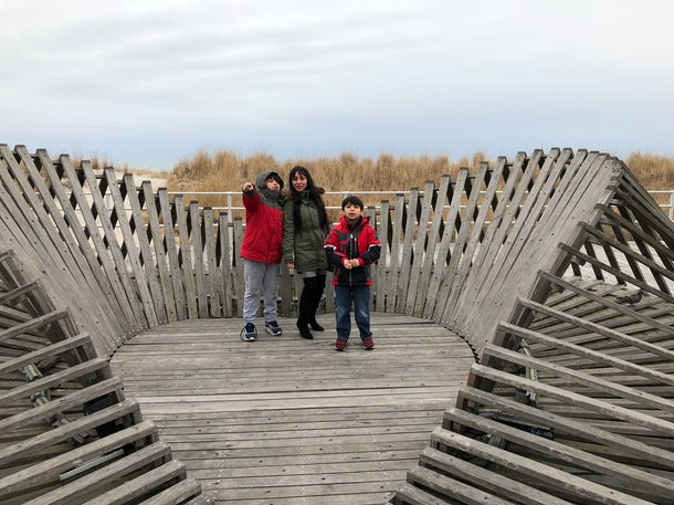 Z.S. stands with her sons in a wooden nest structure.