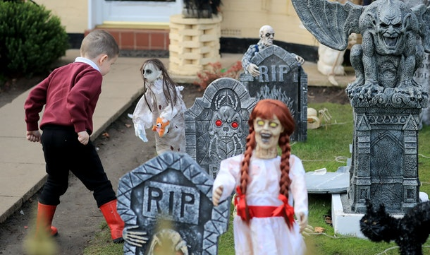 A young boy looks at the Halloween decorations displayed outside a house in Norris Green, Liverpool. (Photo by Peter Byrne/PA Images via Getty Images)