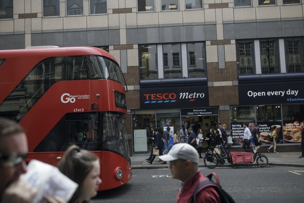 A red double-decker bus drives past a Tesco Plc Metro store London, U.K., on Tuesday, Aug. 6, 2019.