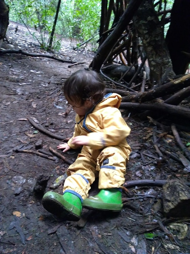 A picture of a young child in a rain coat, playing in the forest.