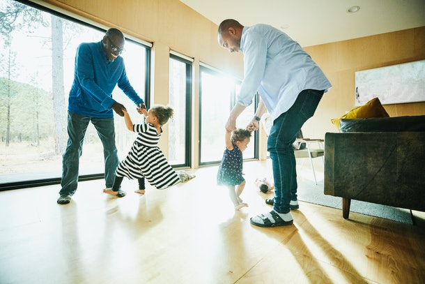 Grandpa and grandchildren play in living room.