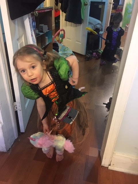 A small child rides a broomstick like a witch.