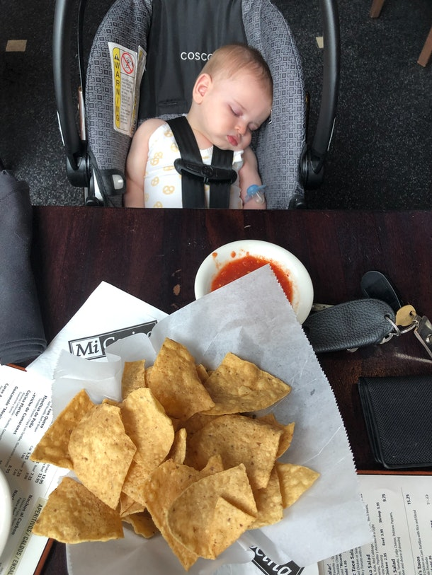 Baby sleeping in car seat next to a restaurant table.