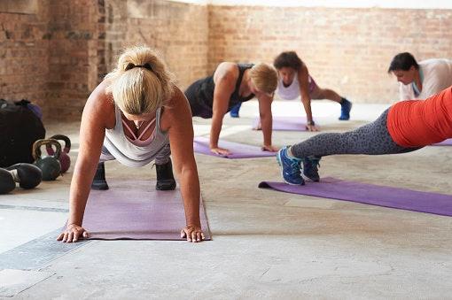 Women in gym doing planks on yoga mats