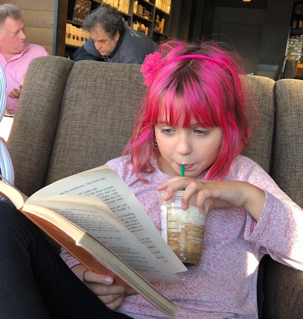 Girl sips drink while reading book