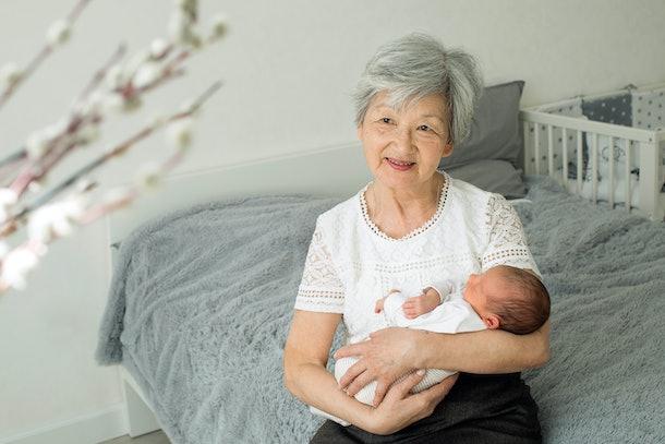 Grandmother cuddling newborn baby.