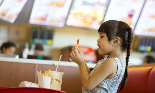 Young girl eats French fries in a food court at a mall