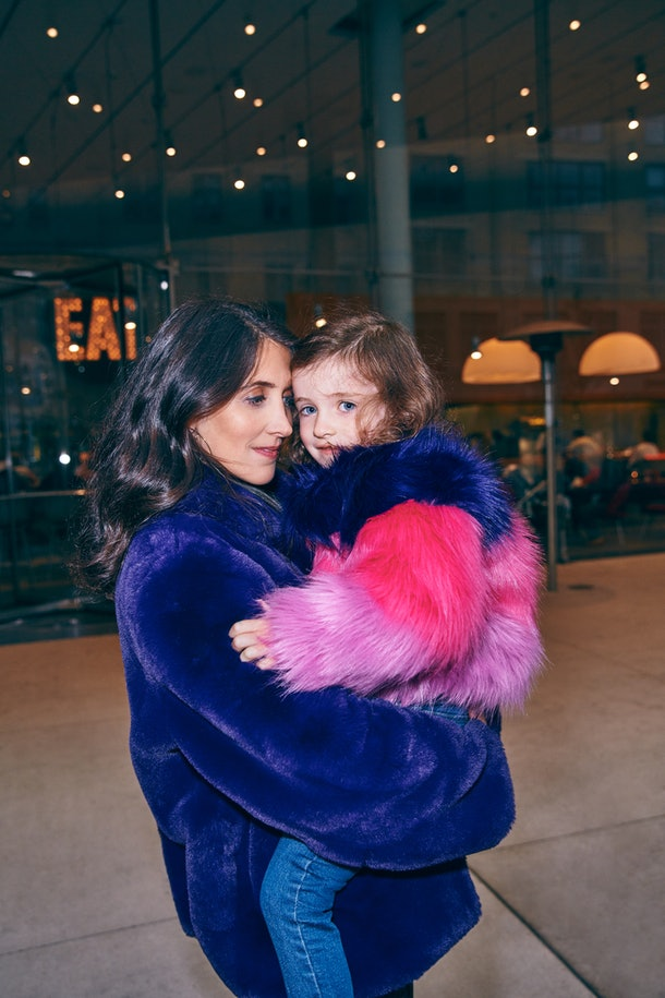 Mother in faux fur coat holds daughter in corresponding jacket