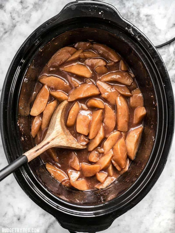 Ariel shot of slow cooker full of gooey, soft, apples in a brown sauce with wooden spoon