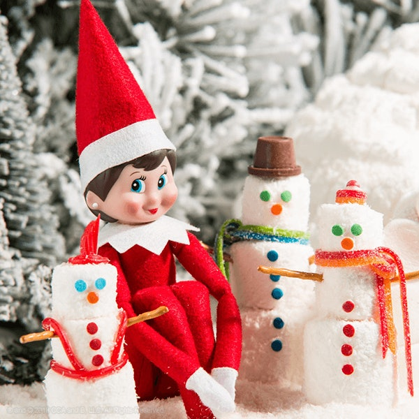 When Does Elf on the Shelf Start; An elf sitting in the snow next to marshmallow snowmen with a Christmas tree behind them
