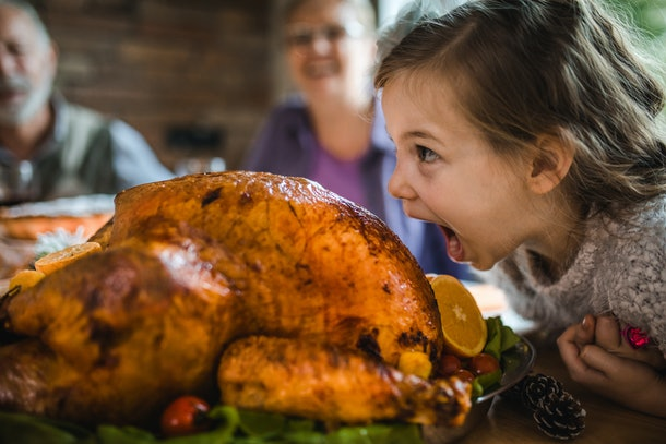A girl pretends to eat a gigantic turkey at Thanksgiving.