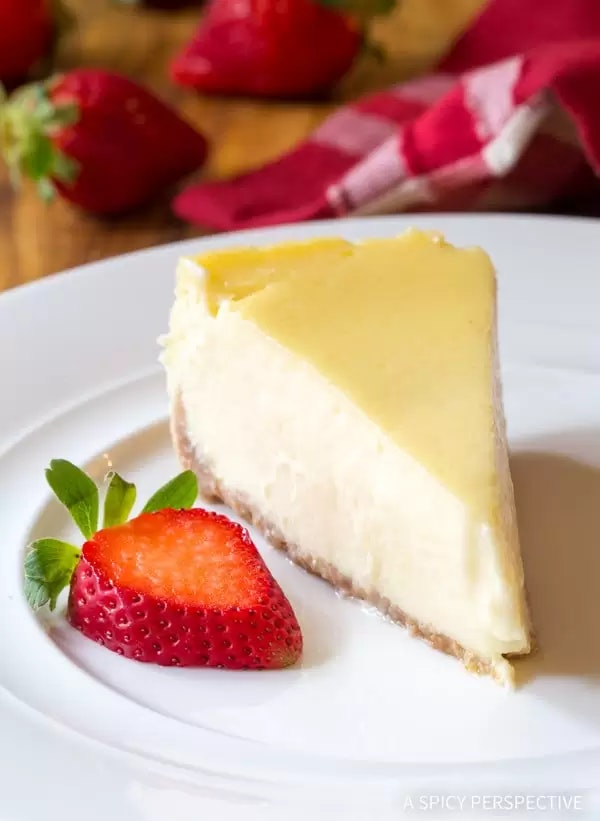 slice of cheesecake on a plate with a slices strawberry on the side