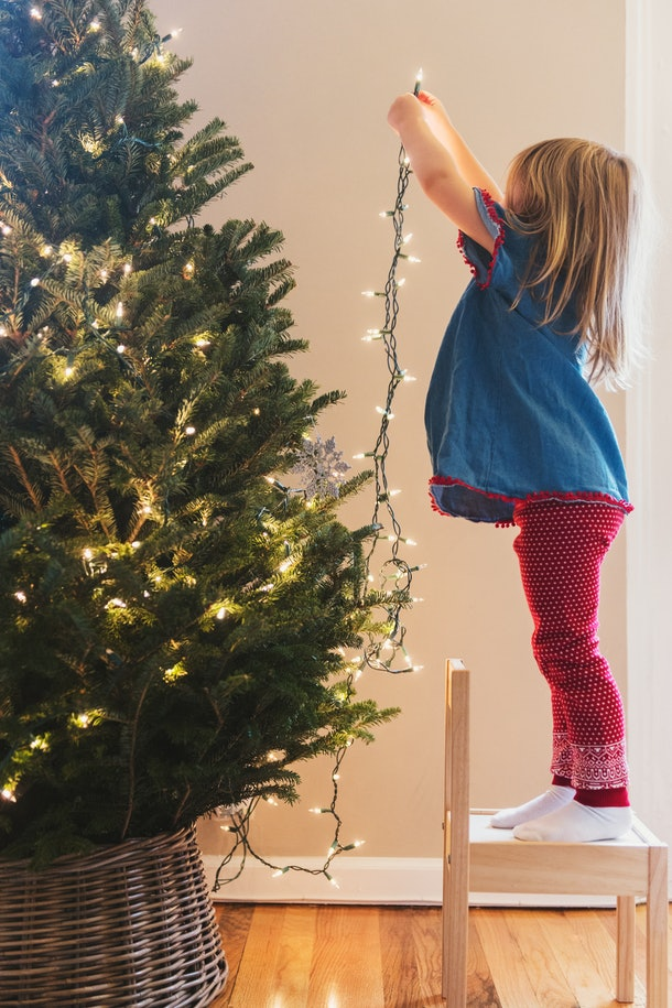 Little girl decorates Christmas tree
