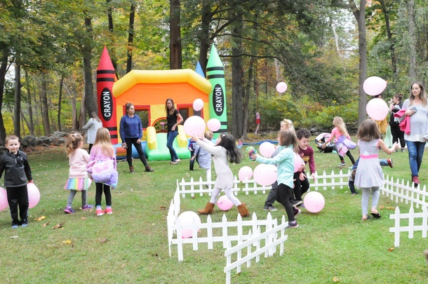 Children play with balloons in front of a jumping castle