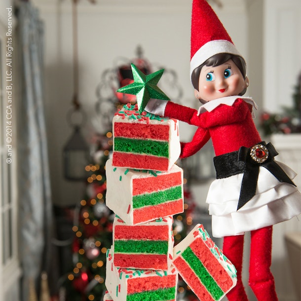 elf on the shelf standing next to a tower of cake bites