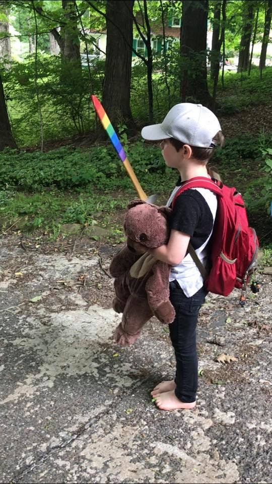 A picture of the author's young son, standing at the edge of the family driveway defiantly, holding a sword, a teddy bear, and wearing a red backpack.