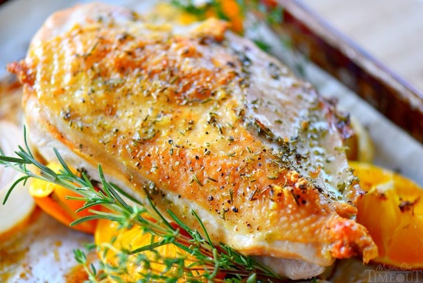 close up of sheet pan  roasted turkey on bed of rosemary and orange