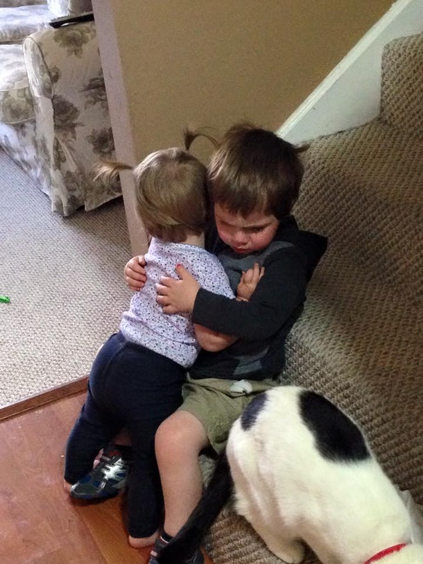 Two young children, siblings, hugging at the foot of their family home's stairs.