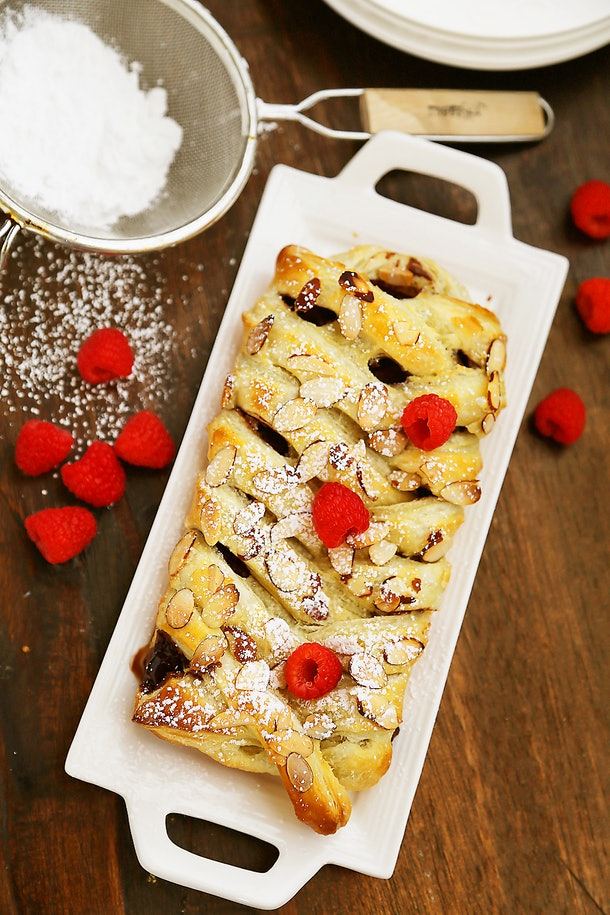 Thanksgiving sheet pan desserts, chocolate almond puff pastry braid with powdered sugar and raspberries on top on a white serving platter