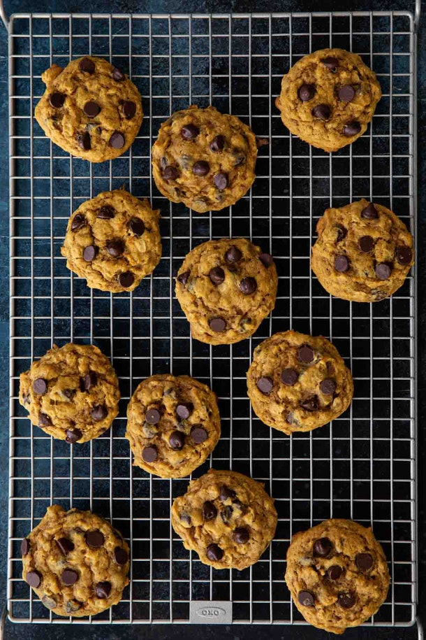Thanksgiving sheet pan desserts, oatmeal pumpkin chocolate chip cookies sitting on a cooling rack with a dark background