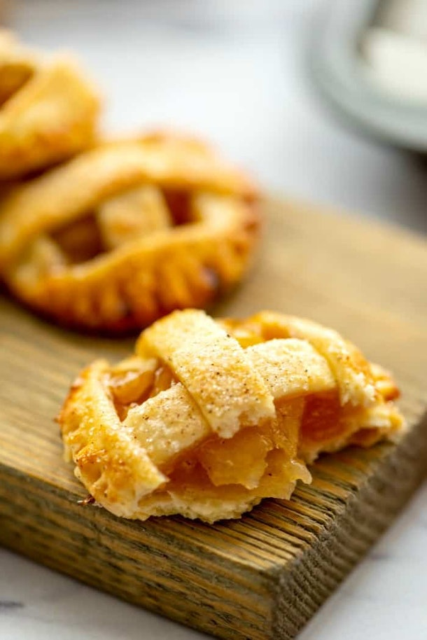 Thanksgiving sheet pan desserts, caramel apple pie cookies laying on a wooden cutting board, one cookie has a bite taken from it