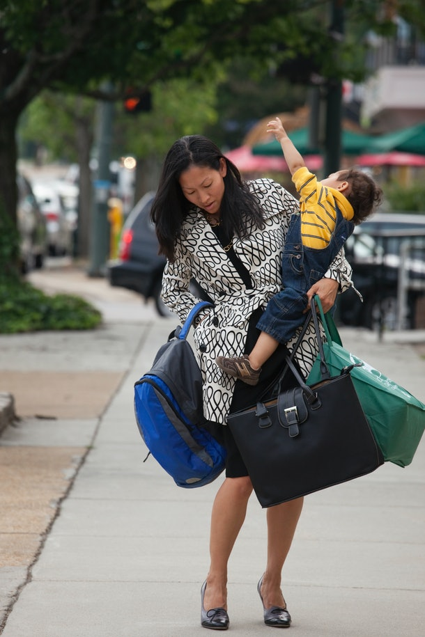 A mother struggles with carrying bags and her child.