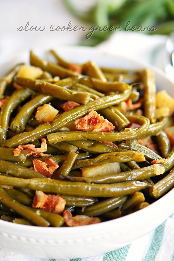 close up shot of green beans with chunks of bacon in a white bowl